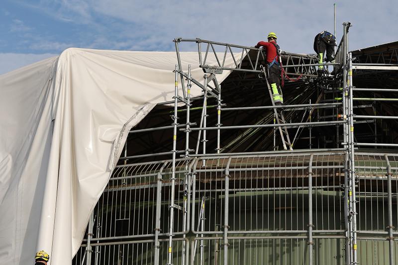 Die Einhausung des Rotundengerüsts wird von Arbeitern entfernt