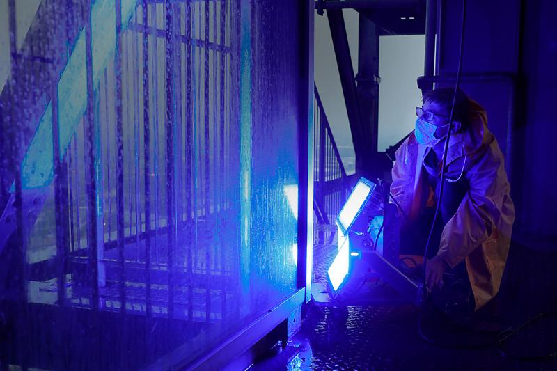 Ein Techniker richtet einen blauen Spor auf die Außenhülle des Gasometers