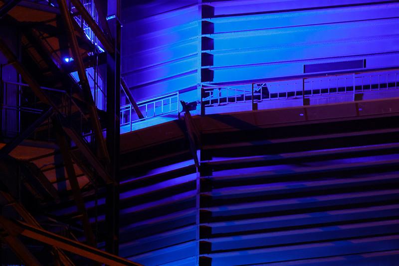 Die Außenhülle des Gasometers wird in zwei unterschiedlichen Blautönen angestahlt