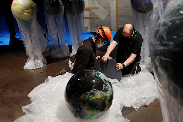 Zwei Mitarbeiter kontrollieren den Fuß eines Globusses