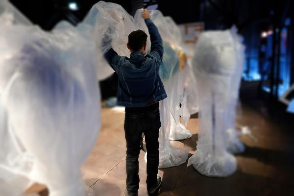 Ein Mitarbeiter kämpft mit der Verpackungsfolie der Globen.