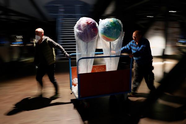 Zwei Globen werden durch zwei Mitarbeiter zu ihrem Bestimmungsort gebracht