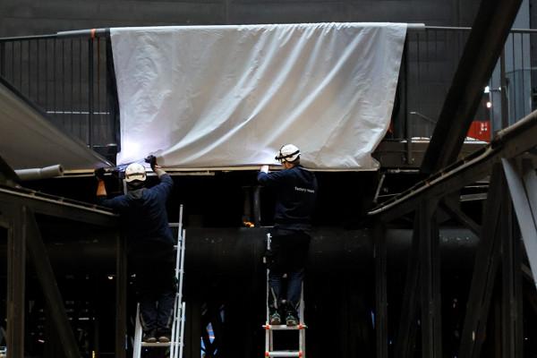 Zwei Arbeiter auf Leitern bereiten eine Stoffbahn vor.