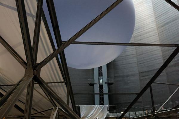 Die riesiege Erdkugel im Hintergrund, Stoffbahnen als Abtrennung zum weiteren Ausstellungsraum im Vordergrund.