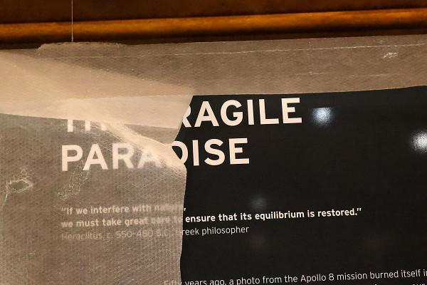 """Das Foto zeigt den halb hinter Folie verborgenen Schriftzug """"Das zerbrechliche Paradies"""" in englischer Sprache"""