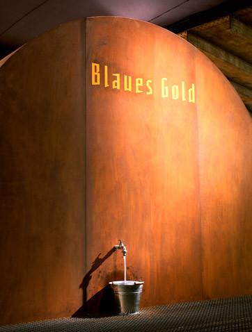 Großes halbrundes Fass mit goldener Blaues Gold Aufschrift. Darunter ein geöffneter Wasserhahn mit einem Einer der das Wasser auffängt.
