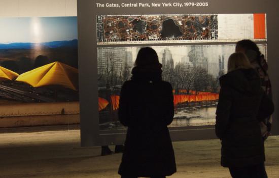Foto zwei im Vordergrund stehender Personen beim Betrachten von einer großen grauen Tafel mit Fotos.