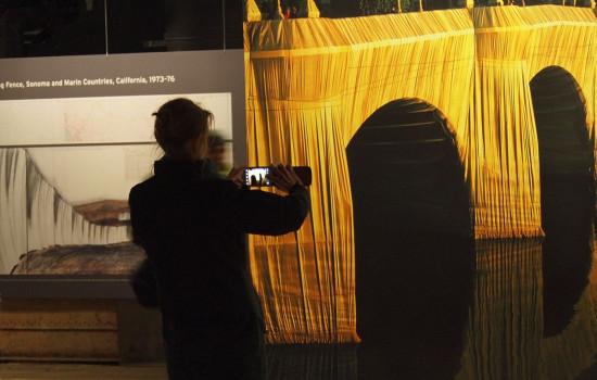 Verschwommenes Foto von einer im Vordergrund stehenden Person, die mit dem Handy ein großes Bild von einer gelben Brücke – Das goldene Leuchten der verhüllten Pont Neuf – fotografiert.