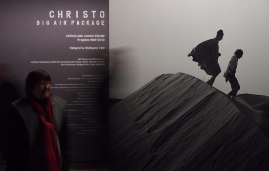 Eine Person vor einer Tafel mit einem grauen Bild von zwei Personen auf einer Düne und linksstehendem Text über CHRISTO – BIG AIR PACKAGE