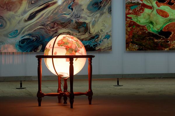 Globus vor einer Ausstellungswand mit zwei Fotos