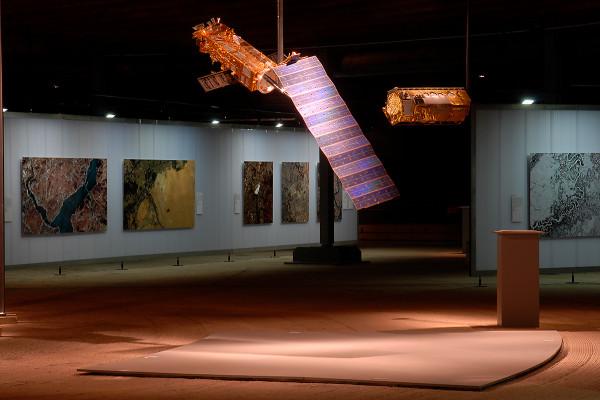 Ein Satellit hängt vor verschiedenen großformatigen Ausstellungsbildern