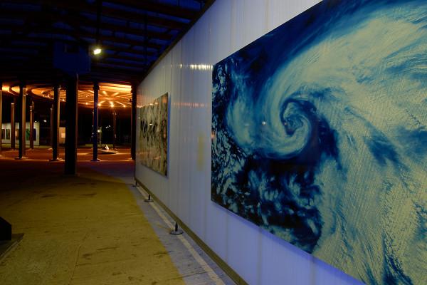 Zwei groformatige Fotos hängen an einer Ausstellungswand. Im Hintergrund ist ein Meteroit zu sehen