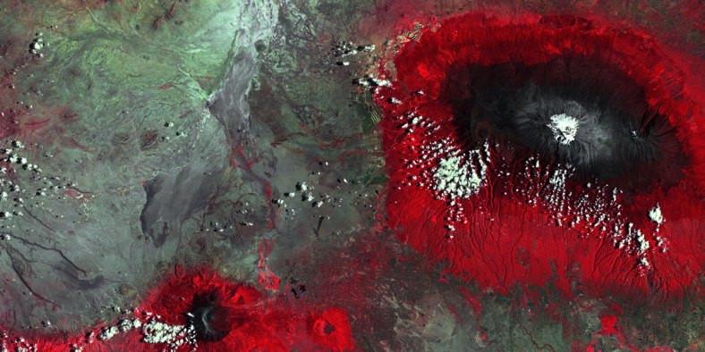 Von oben fotografierter Berg – der Kilimandscharo – mit weißer Spitze und rotem Gelände