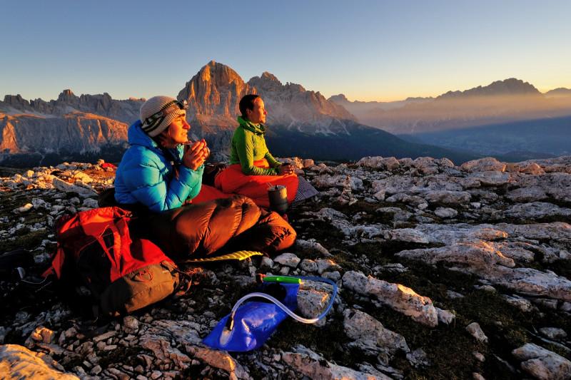 Ein Foto von zwei in dicken Jacken und Schlafsäcken auf Gestein sitzenden Personen beim Sonnenaufgang in den Dolomiten.