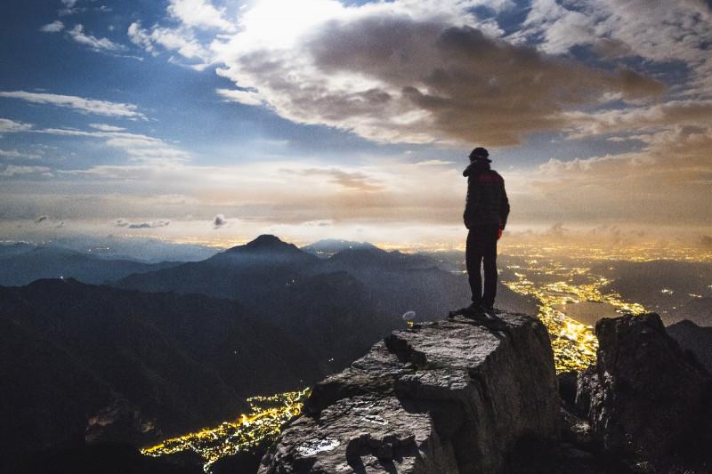 Foto von einem Wanderer auf einem Felsen auf einer Bergspitze mit Blick auf andere Berge und Lichter einer Stadt bei Dämmerung