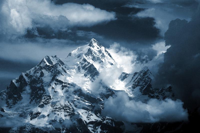 Blick auf ein Bergmassiv mit Wolken und Sonnenschein