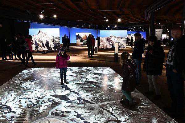 Ein Kind steht auf der Bodenprojektion des Himalaya in der unteren Ausstellungsebene des Gasometers