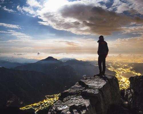 Foto von einem Wanderer auf einem Felsen auf einer Bergspitze mit Blick auf andere Berge und Lichter einer Stadt bei Dämmerung.