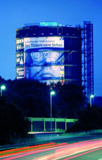 Fotografie vom Gasometer am Abend mit dem Plakat der Ausstellung der Traum vom Sehen.