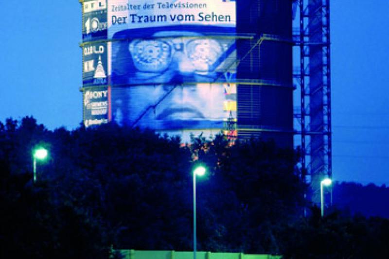 Fotografie vom Gasometer am Abend mit dem Plakat der Ausstellung der Traum vom Sehen