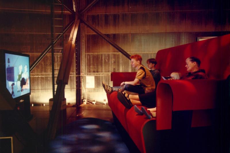 Drei Personen auf einem übergroßem rotem Sofa sitzend und auf den vor ihnen stehenden Fernseher schauenden.