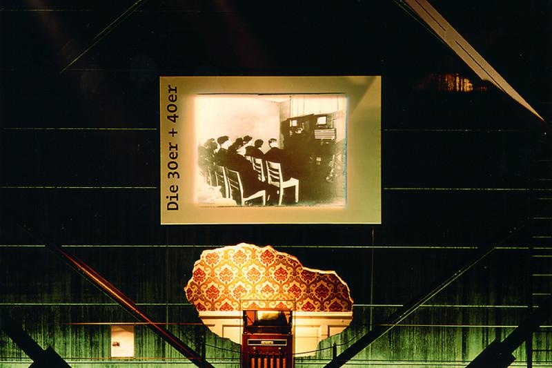 Ein Radio der 1930er Jahre vor zeitgenössischer Tapete als Exponat