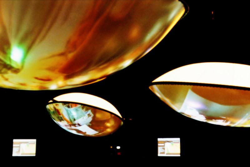 drei gold-weiße Lampen und zwei Bildschirme vor schwarzem Hintergrund