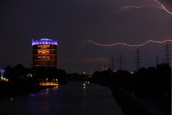 Landschaftsaufnahme des Gasometers bei Gewitter mit Blitzen