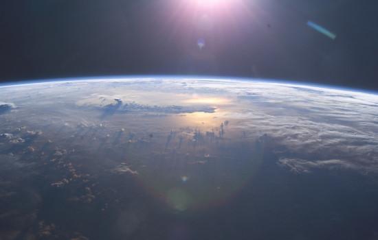 Aus dem Weltraum von oben fotografierter Ausschnitt von der Oberfläche der Erde mit von oben kommenden Sonnenstrahlen.