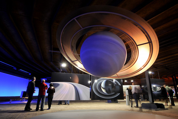 Besucher betrachrten Planetenskulpturen und großformatige Bilder