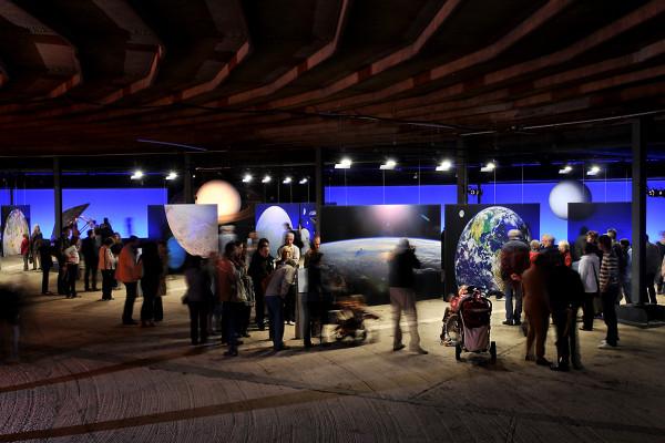 Besucher vor Exponaten und Fotografien