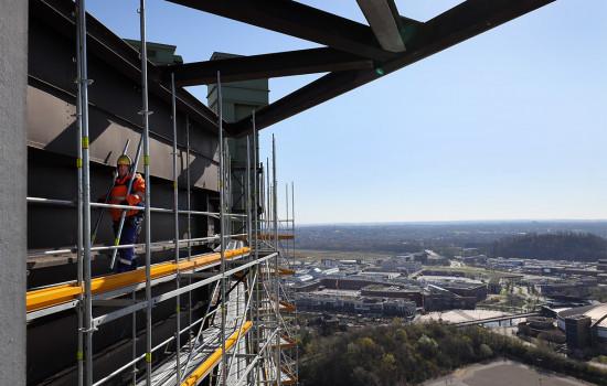 Ein Gerüstbauer stellt in luftiger Höhe das Fassadengerüst des Gasometers fertig.