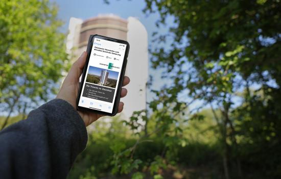 Mobiltelefon mit dem Gasometer-Newsletter auf dem Display. Im Hintergrund ist der Gasometer zu sehen.