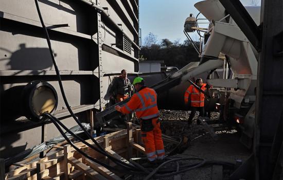 Drei Arbeiter füllen Beton aus einem Betonmischer in die Verschalung für das Fundament des Gasometers.